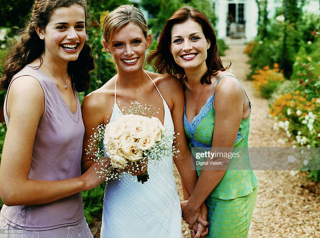 Portrait of a Bride Holding a Bouquet of White Roses Standing Between Her Two Bridesmaids