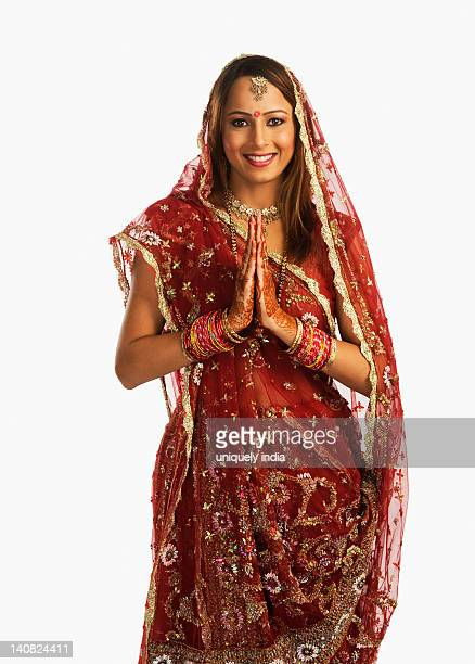 Portrait of a bride in traditional wedding dress standing in prayer position