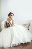 Portrait of a bride with a bouquet in a bright room on a white sofa