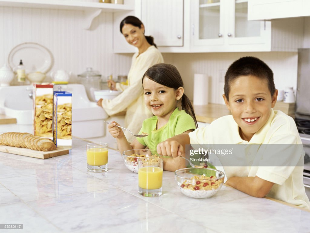 portrait of a brother and his sister eating their breakfast : Stock Photo