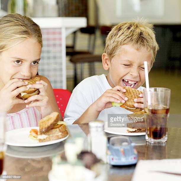 portrait of a brother and sister eating sandwiches together
