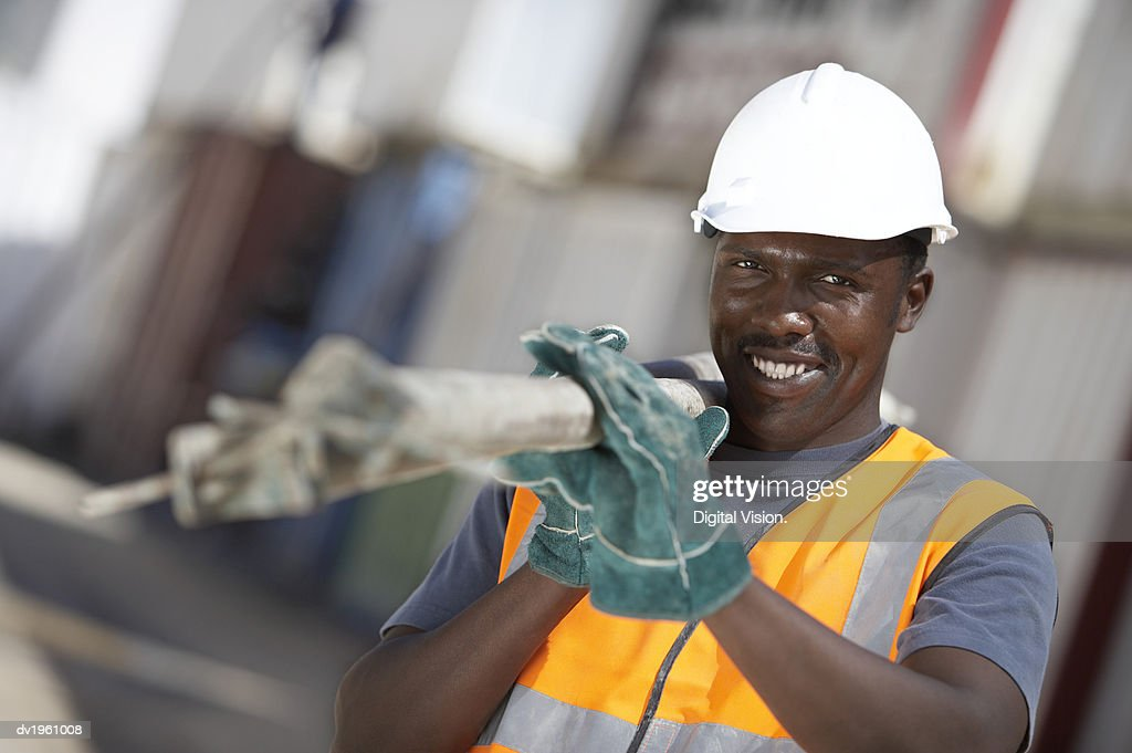 Portrait of a Builder Wearing a Hard Hat Carrying Scaffolding Poles Over His Shoulder