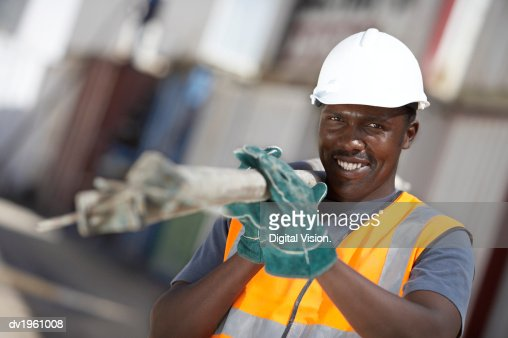 Portrait of a Builder Wearing a Hard Hat Carrying Scaffolding Poles Over His Shoulder : Stock Photo