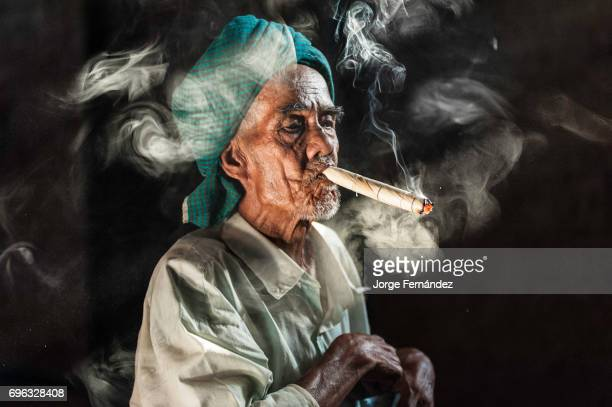 Portrait of a Burmese man with a typical handkerchief on his head smoking a big cigar made out of tobacco and corn leaves