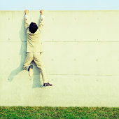 Portrait Of A Business Man Climbing On Wall