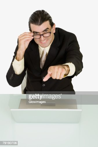 Portrait of a businessman adjusting his eyeglasses and pointing forward : Stock Photo