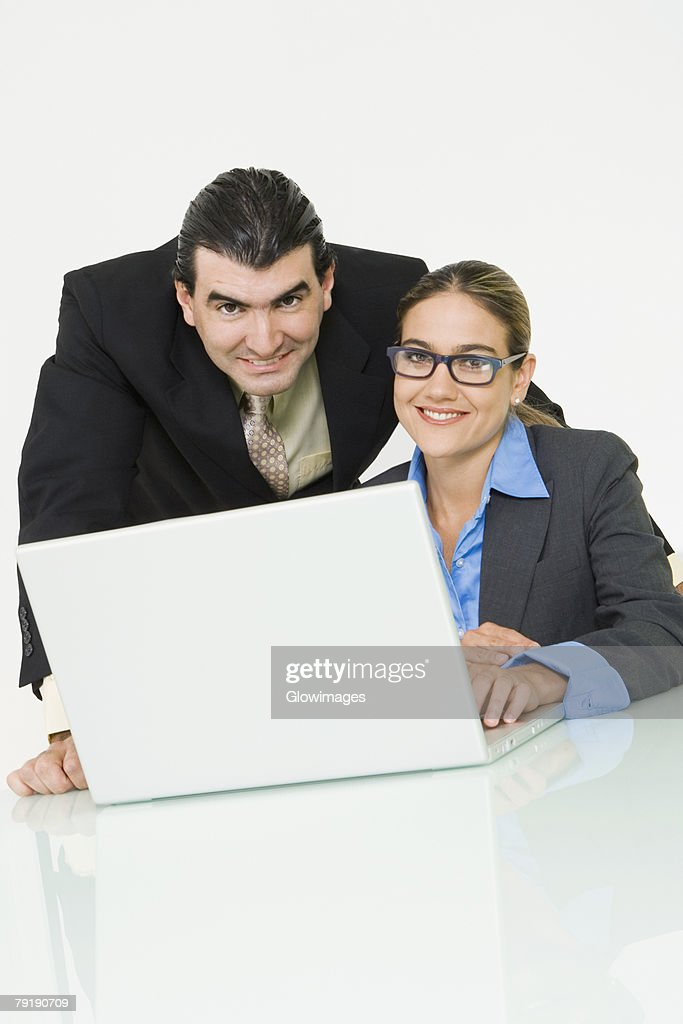 Portrait of a businessman and a businesswoman smiling in front of a laptop : Foto de stock