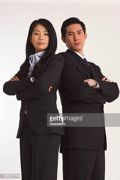 Portrait of a businessman and a businesswoman standing back to back