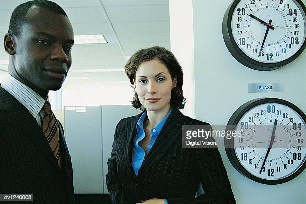 Portrait of a Businessman and a Businesswoman Standing Next to Time Zone Wall Clocks