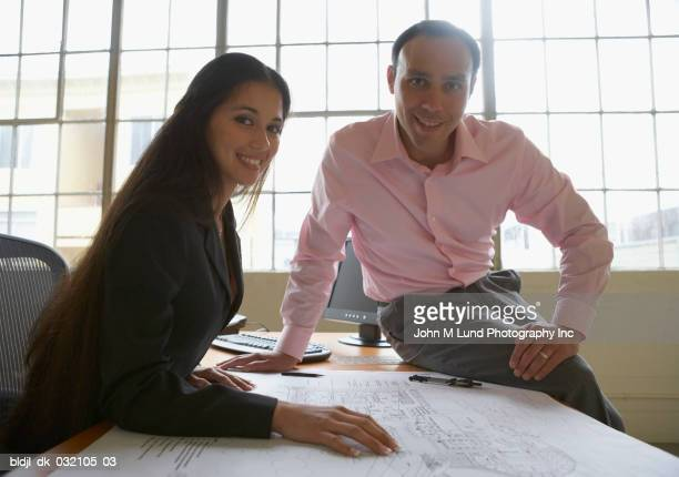 Portrait of a businessman and a businesswoman with blueprints on a table