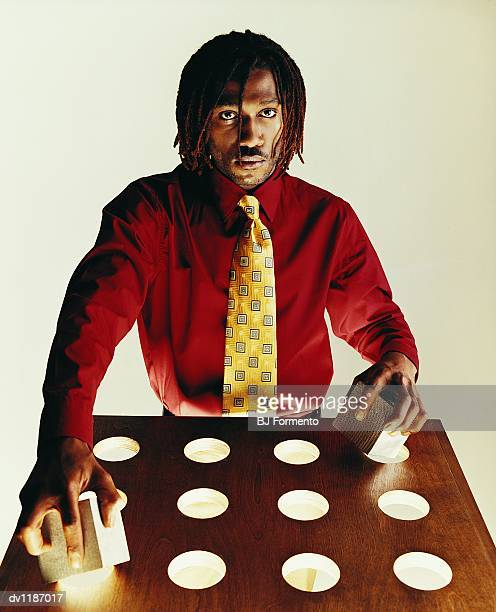 Portrait of a Businessman Attempting to Insert Wooden Cubes Into Circular Holes