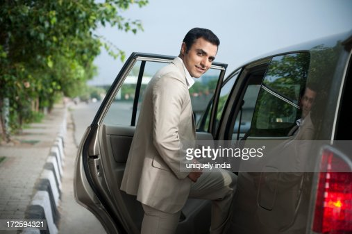 Portrait of a businessman getting into a car and smiling
