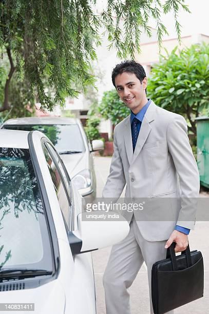 Portrait of a businessman getting into a car