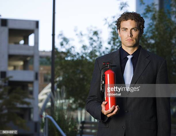 Portrait of a businessman holding a fire extinguisher