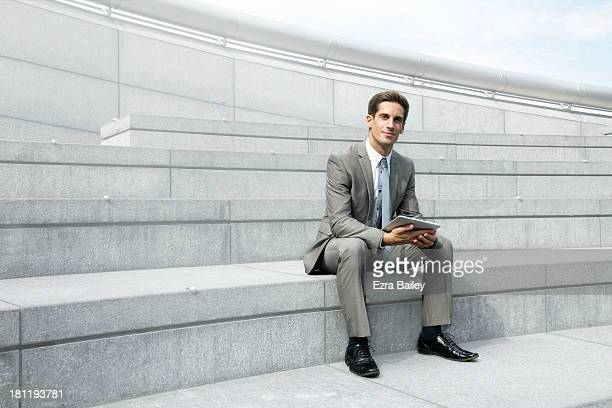 Portrait of a businessman holding a tablet outside