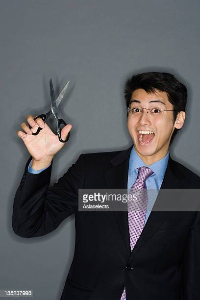 Portrait of a businessman holding scissors and laughing