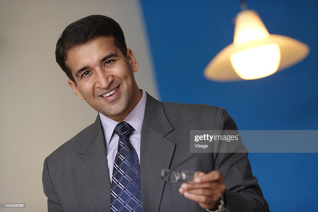 Portrait of a businessman holding spectacles : Stock Photo
