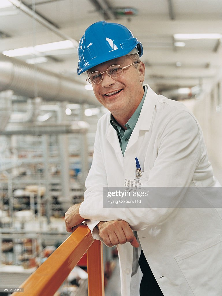 Portrait of a Businessman in a Factory Wearing a Workcoat : Stock Photo