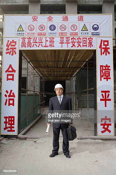 Portrait of a businessman in a hard hat on a construction site, signage behind stresses workplace safety.