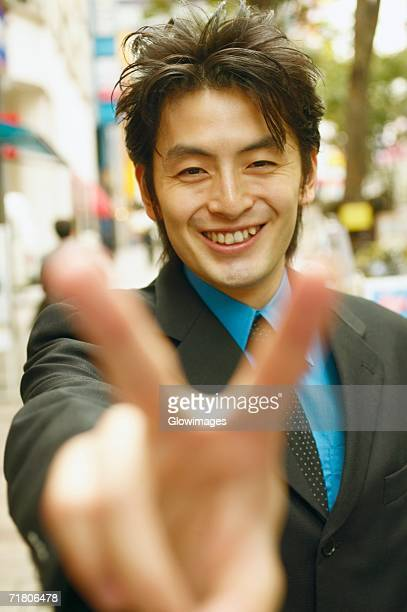 Portrait of a businessman making the peace sign