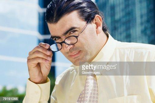 Portrait of a businessman peeking over his eyeglasses : Foto de stock