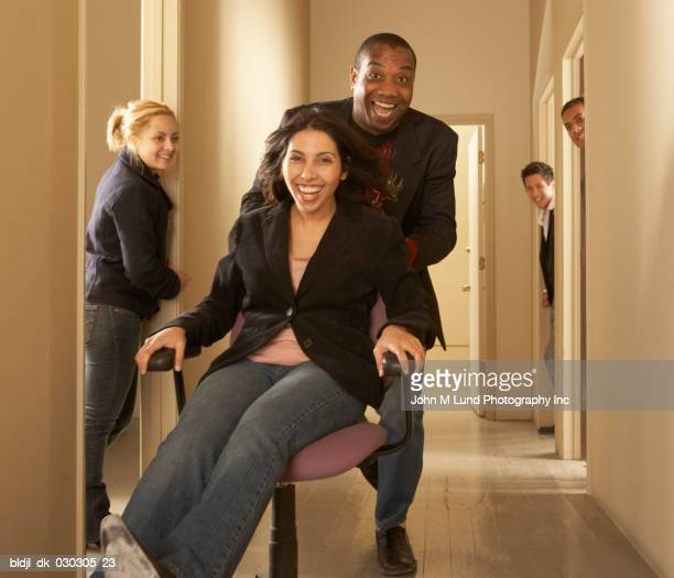 Portrait of a businessman pushing a businesswoman sitting on a chair