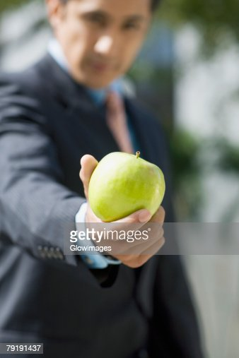 Portrait of a businessman showing a granny smith apple : Stock Photo
