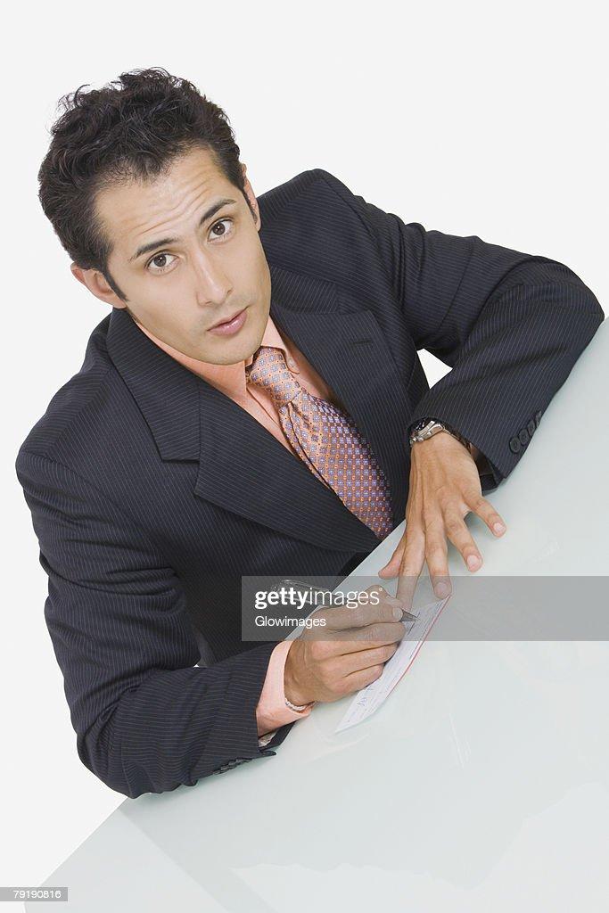 Portrait of a businessman signing a check : Foto de stock