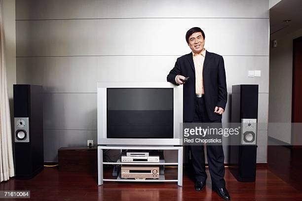 Portrait of a businessman standing by the side of a television smiling