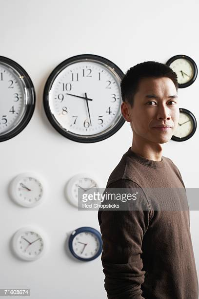 Portrait of a businessman standing in front of clocks on the wall