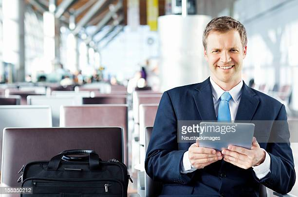 Portrait Of A Businessman Using Tablet Computer At The Airport.
