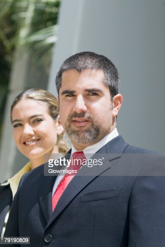 Portrait of a businessman with a businesswoman smiling behind him : Stock Photo