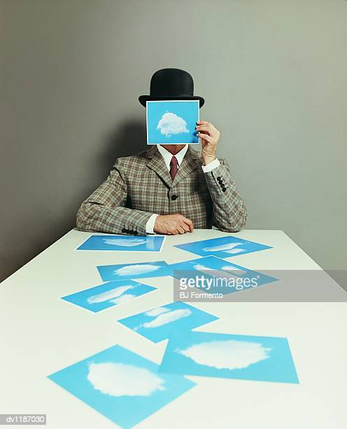 Portrait of a Businessman With an Obscured Face Holding a Photograph of a Cloud