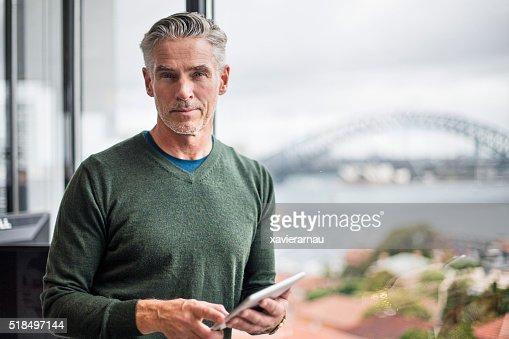 Retrato de un hombre de negocios con tableta digital en oficina