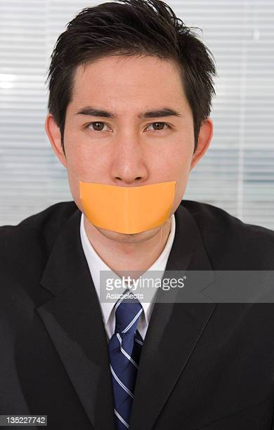 Portrait of a businessman with duct tape on his lips