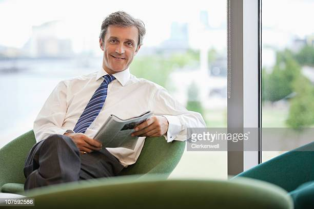 Portrait of a businessman with magazine sitting at office cafeteria