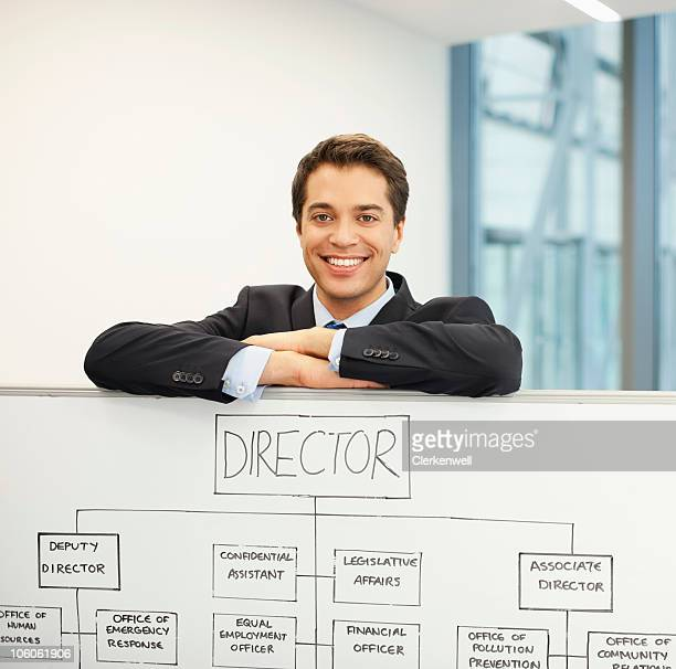 Portrait of a businessman with the organization tree on whiteboard