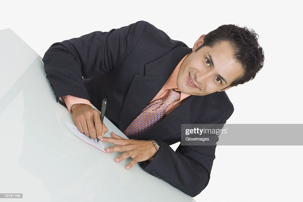 Portrait of a businessman writing on a sheet of paper and smiling : Foto de stock