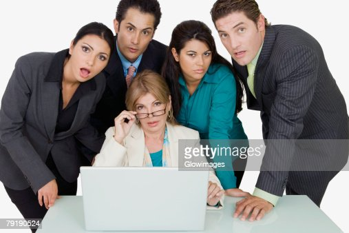 Portrait of a businesswoman adjusting her eyeglasses and two businesswomen with two businessmen standing beside her : Stock Photo