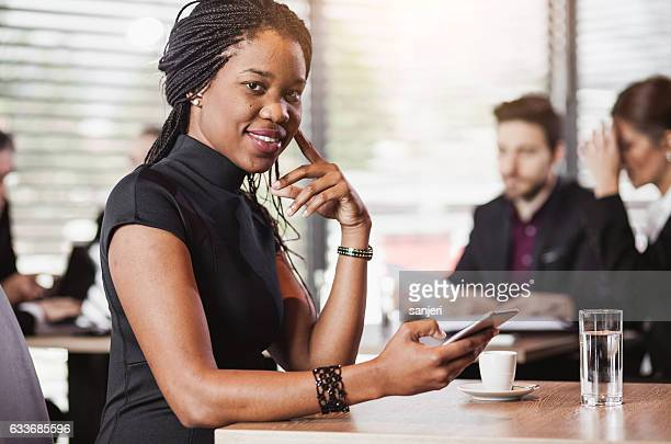 Portrait of a Businesswoman at a Cafe Holding Smart Phone