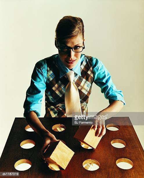 Portrait of a Businesswoman Attempting to Insert Wooden Cubes Into Circular Holes