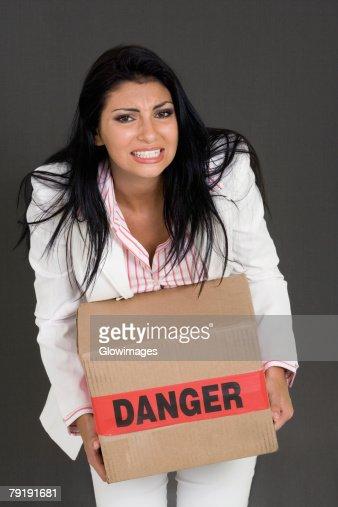 Portrait of a businesswoman carrying a cardboard box : Stock Photo