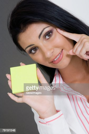 Portrait of a businesswoman holding a blank adhesive note and smiling : Foto de stock