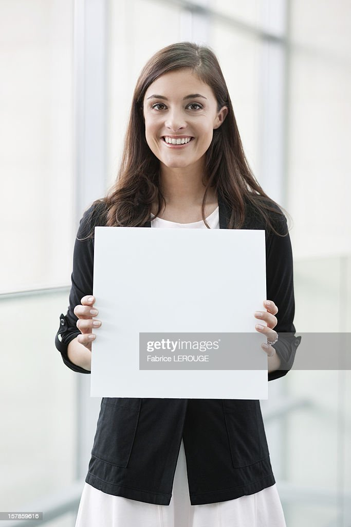 Portrait of a businesswoman holding a blank placard and smiling in an office : Stock-Foto
