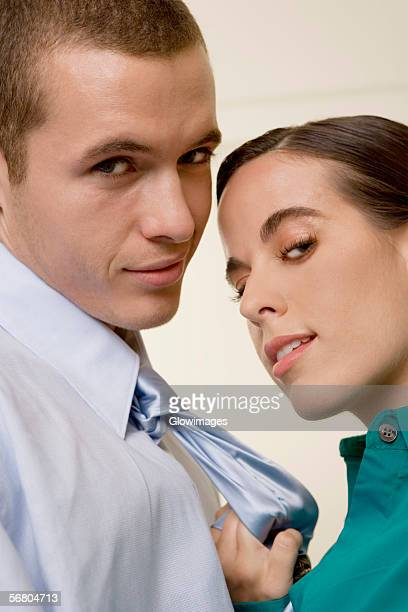 Portrait of a businesswoman holding a businessman by his tie