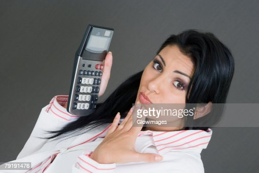 Portrait of a businesswoman holding a calculator and making a face : Foto de stock