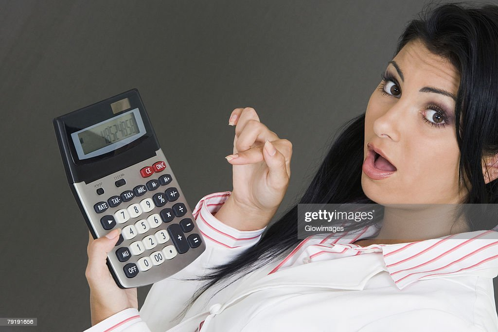 Portrait of a businesswoman holding a calculator and pointing at it : Foto de stock