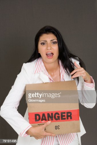 Portrait of a businesswoman holding a cardboard box : Stock Photo