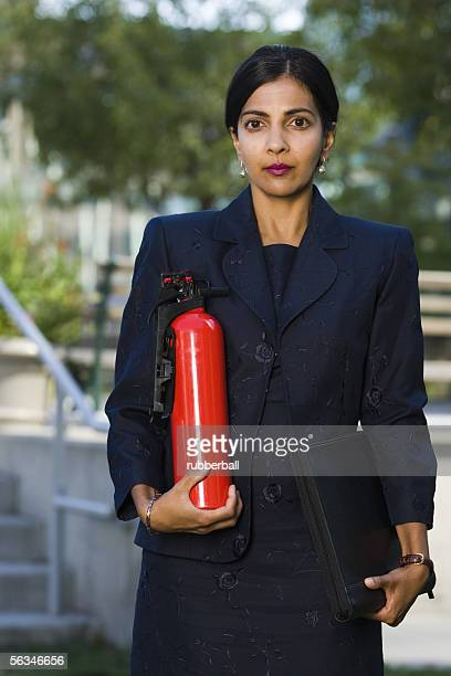 Portrait of a businesswoman holding a fire extinguisher