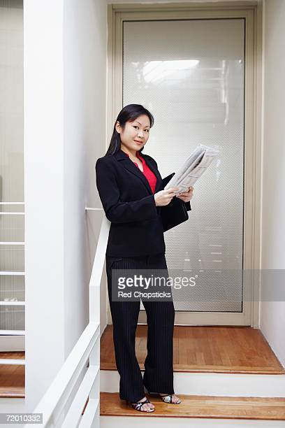 Portrait of a businesswoman holding a newspaper and smiling